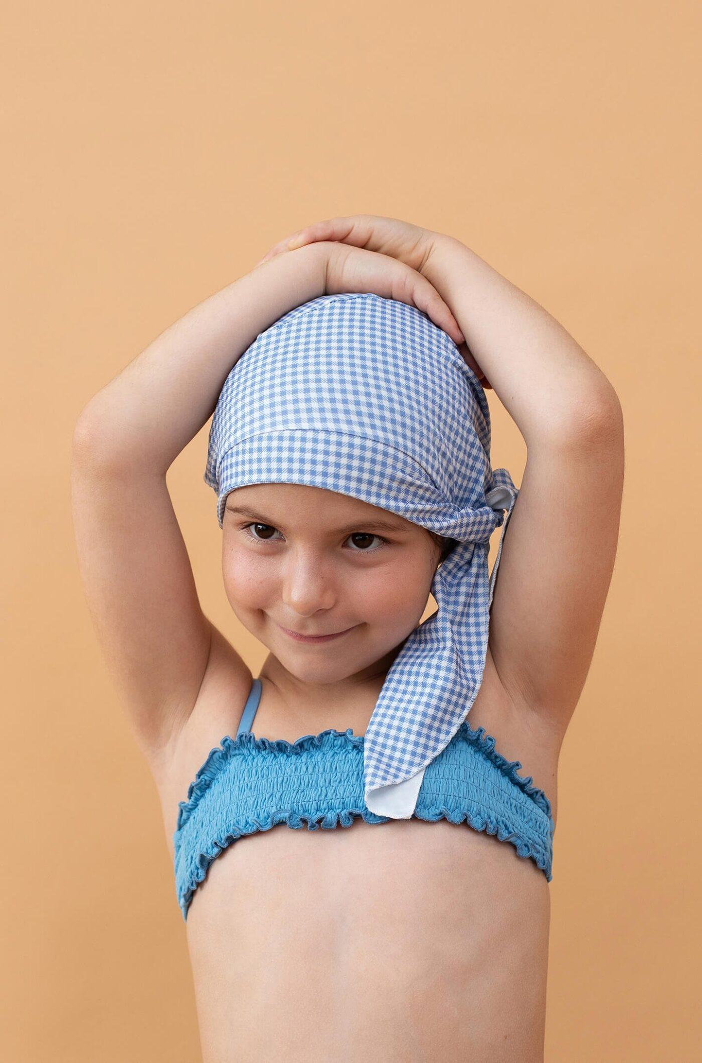 Niña con gorro de ducha cuadros azules y blancos