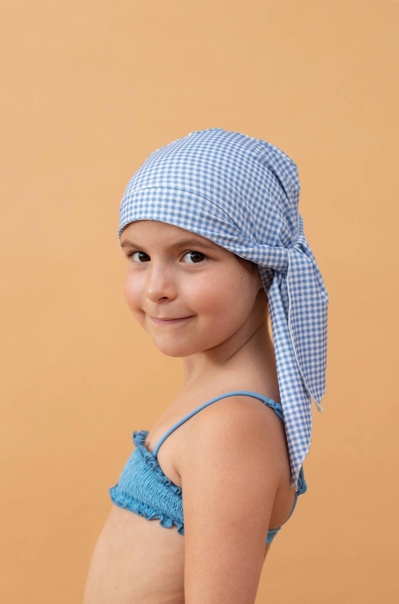 Niña con gorro de ducha de cuadros azules y blancos