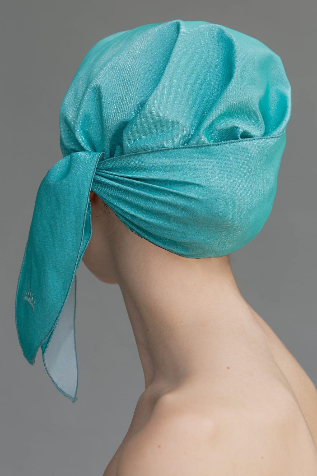 Chica con gorro de ducha visto por detrás color turquesa