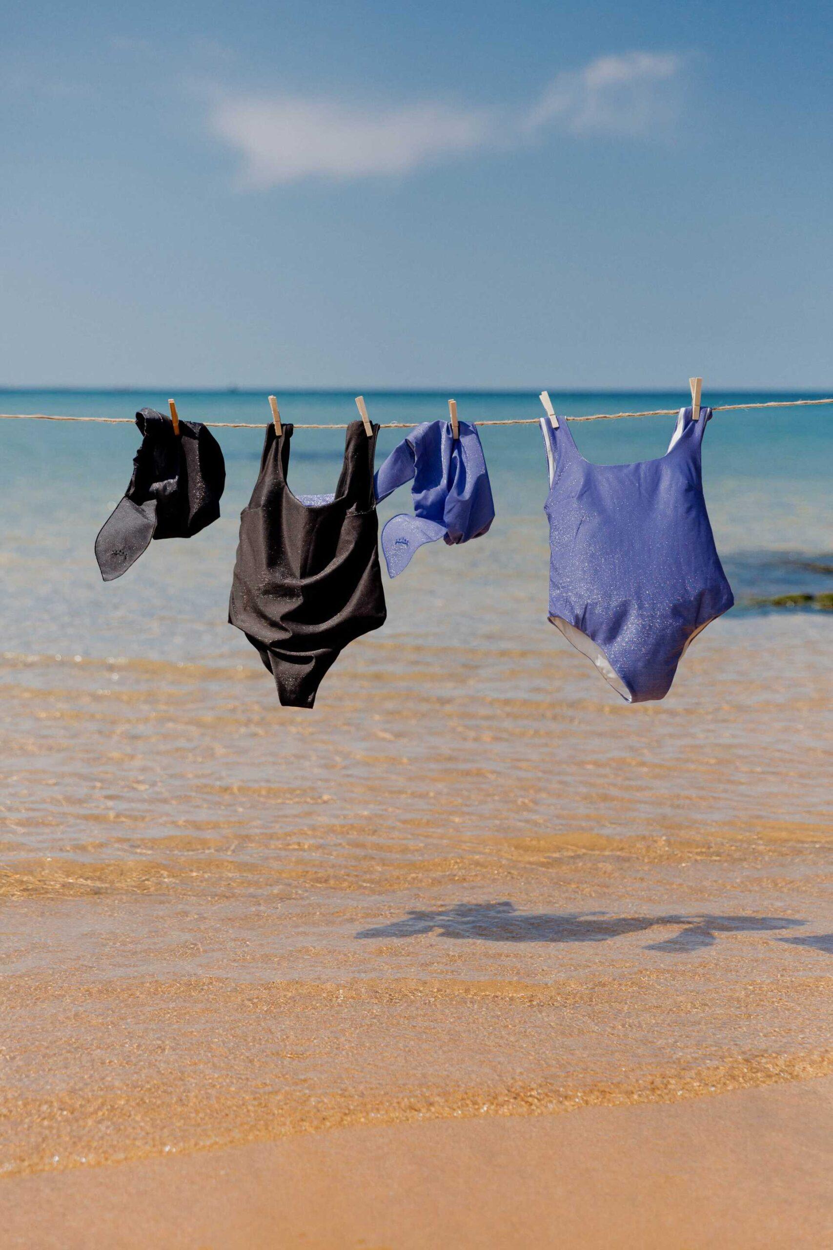 Bañador negro y bañador lavanda con gorro de ducha a juego colgados en tendedero en la playa